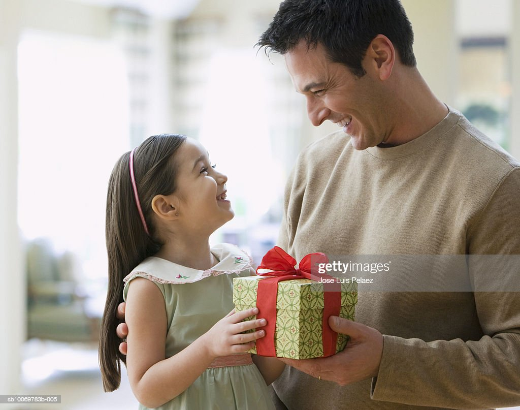 Girl (4-5) giving gift to father : Stock Photo