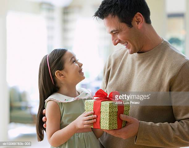 Girl (4-5) giving gift to father