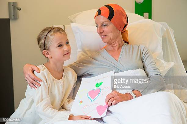 Girl giving greeting card to her illness mother