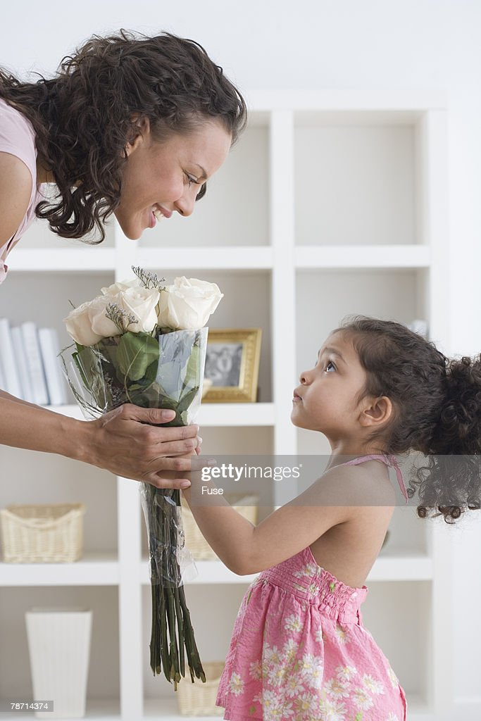 Girl Giving Her Mother Bouquet of Roses : Stock Photo