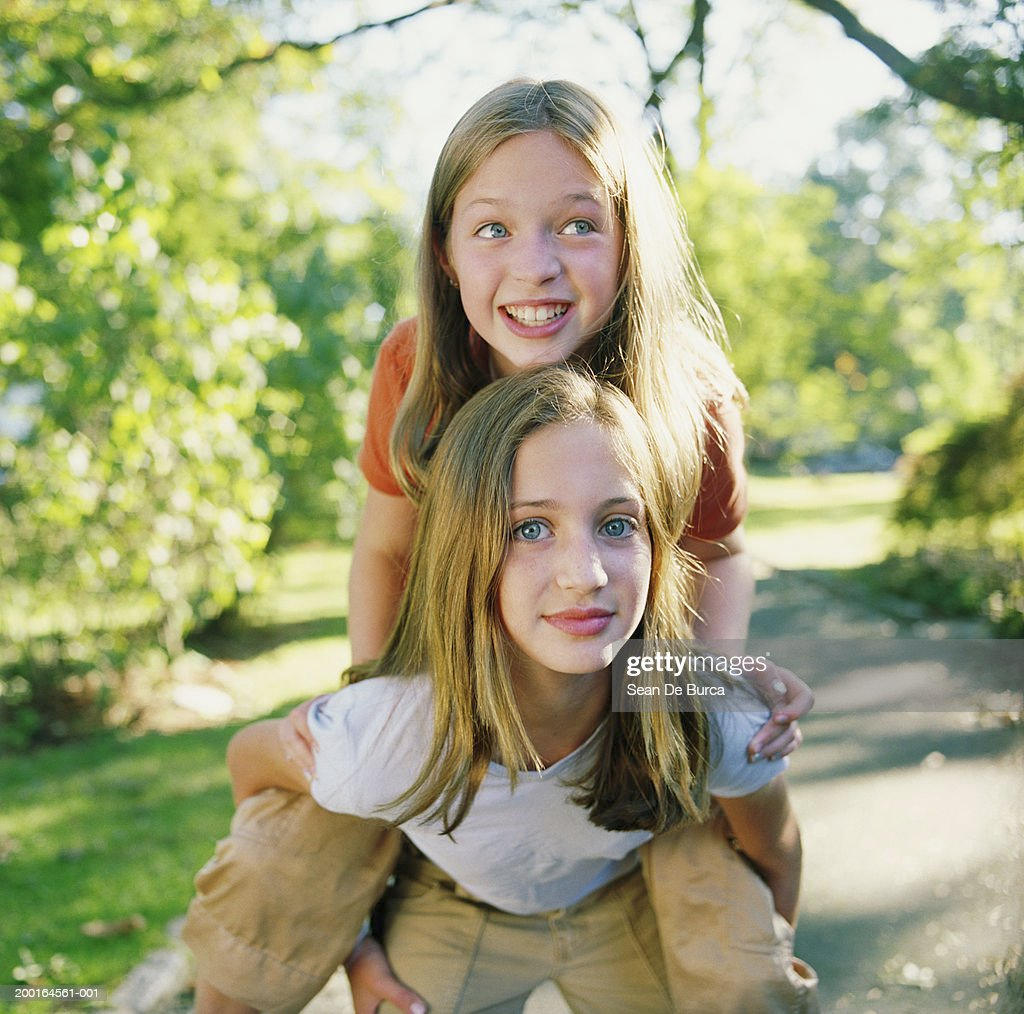 Girl Giving Sister Piggyback Ride Spring Stock Photo