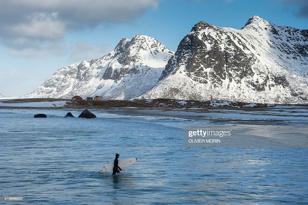 A girl goes out the water at the snowy beach of Flackstad, in Lofoten archipelago, Arctic Circle, on March 13, 2016 Surfers from all over the world come to Lofoten islands to surf in extrem conditions. Ocean temperature is 5-6 °C, air temperature around 0°C in spite of a weather very unstable. / AFP / OLIVIER