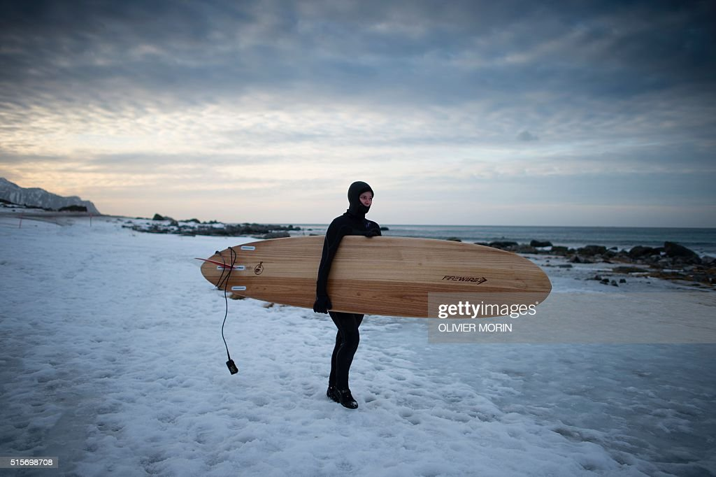 A girl goes to surf at the snowy beach of Flackstad, near Ramberg, in Lofoten archipelago, Arctic Circle, on March 12, 2016. Surfers from all over the world come to Lofoten islands to surf in extrem conditions. Ocean temperature is 5-6 °C, air temperature around 0°C in spite of a weather very unstable. / AFP / OLIVIER