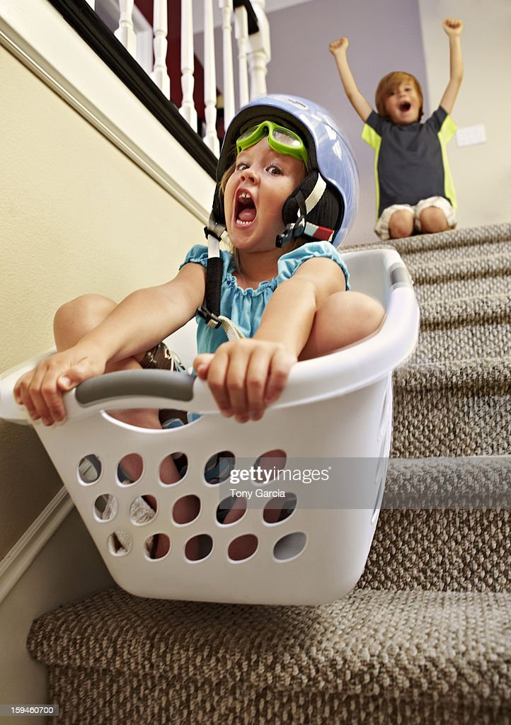 Girl going down stairs in laundry basket : Stock Photo