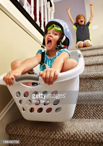 Girl going down stairs in laundry basket