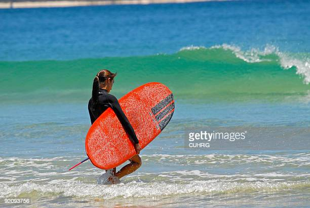 Girl going for a surf in Noosa