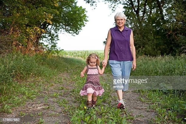 Mädchen gehen Sie zu Fuß auf der Farm mit Oma