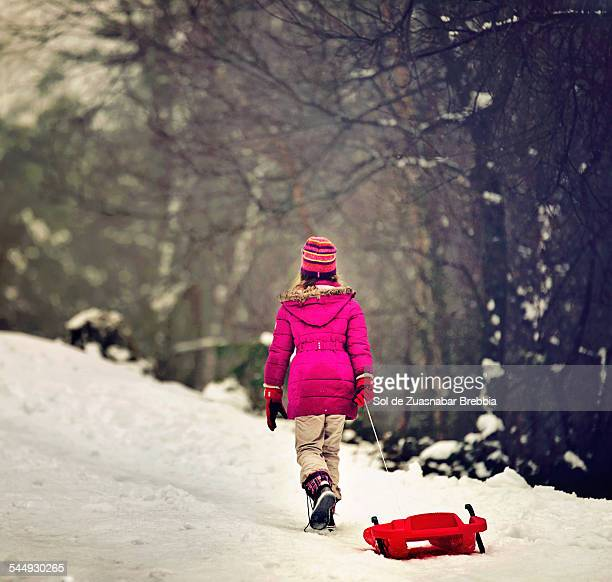 Girl going up a snowy hill dragging a sled