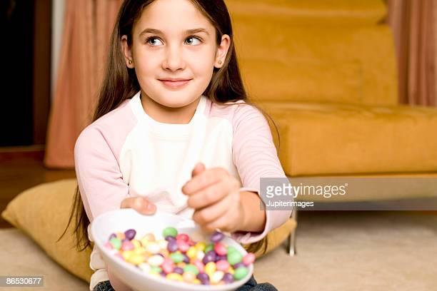 Girl grabbing candy in bowl