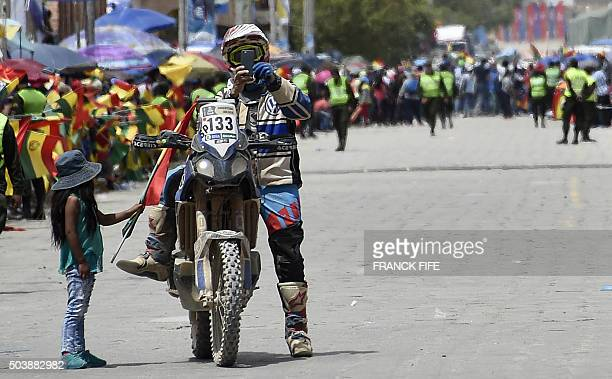 A girl greets Spain's biker Julio Federico Quiroga at the end of the Stage 5 of the Dakar Rally 2016 between Jujuy in Argentina and Uyuni Bolivia on...
