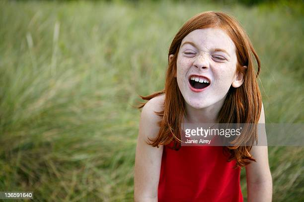 Girl grimacing in tall grass