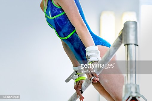 girl gymnast athlete during an exercise horizontal bar in gymnastics competitions : Stock Photo