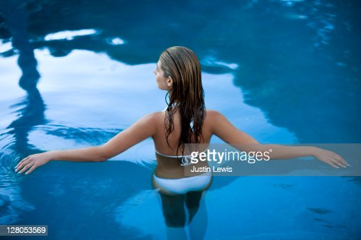 Pool Water girl half in and half out of luxury pool water stock photo | getty
