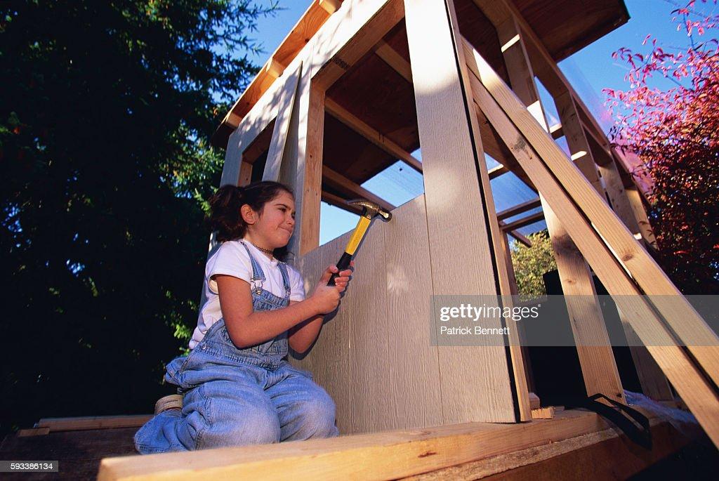Girl Hammering Wood on Tree House