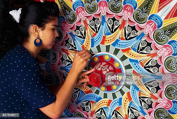 Girl hand painting a wagon wheel Sarchi Norte Costa Rica