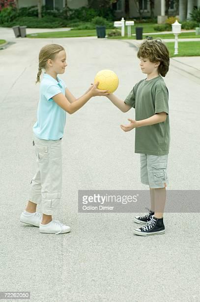 Girl handing boy ball in residential street