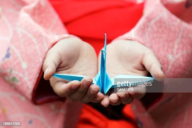 Femme mains tenant un origami crane