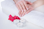 Woman hands with french manicure modern style on towel with red rose petals and candle in beauty salon. Manicure and Beauty concept. Close up, selective focus