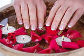 Woman hands with french nails polish style and wooden bowl with water and floating candles and red rose petals. Manicure and Beauty concept. Close up, selective focus