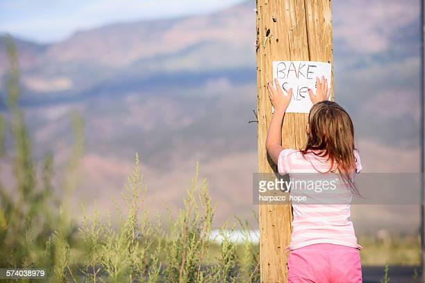 Girl hanging a bake sale sign