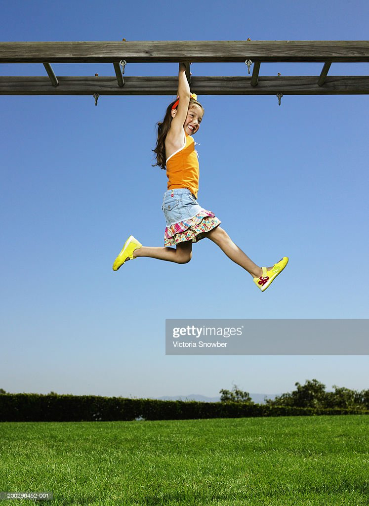 Girl (4-6) hanging from monkey bars