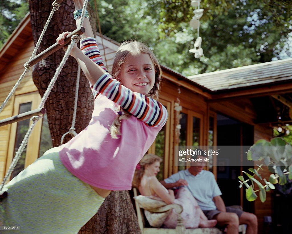 Girl (8-10) hanging from rope ladder, portrait : Stock Photo