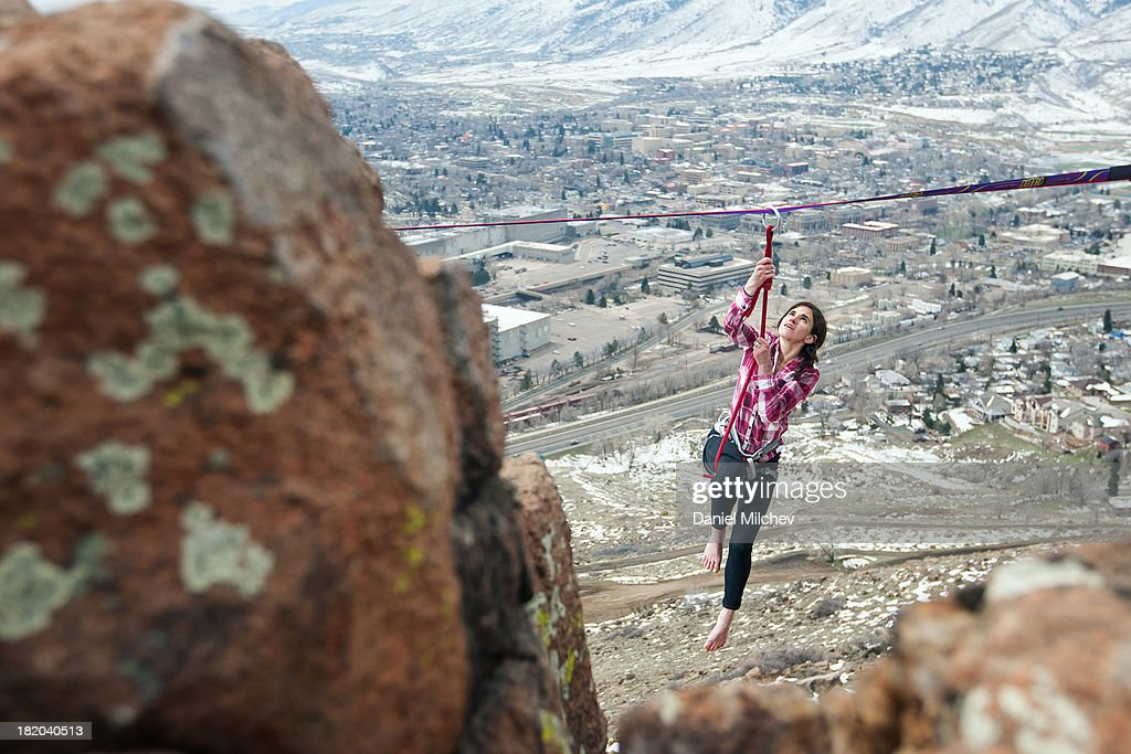 Girl hanging off of a high line, over a small town : Stock Photo