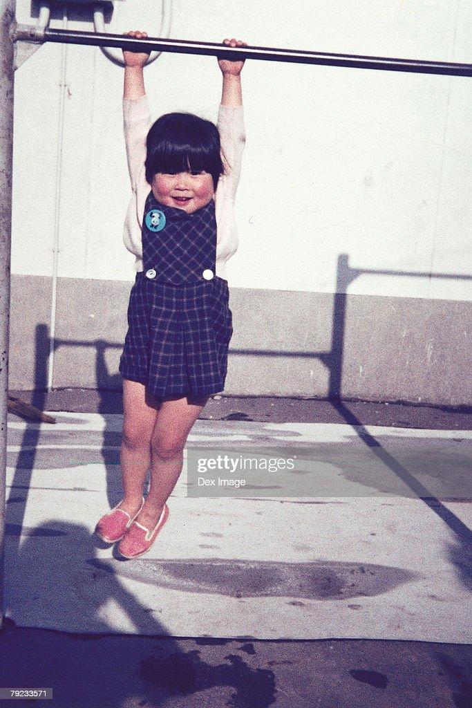 Girl hanging on a monkey bar : Stock Photo