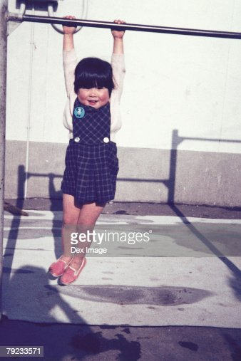 Girl hanging on a monkey bar : Stock Photo