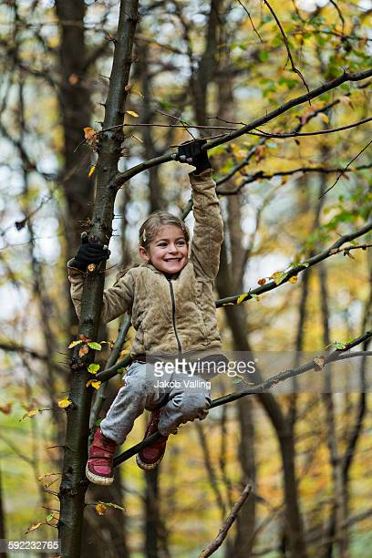 Girl hanging on to tree branch in autumn forest