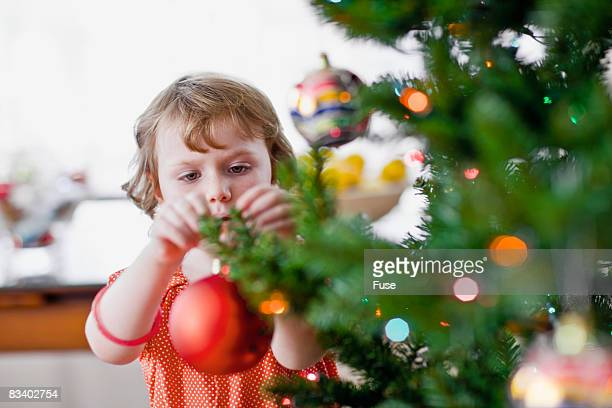 Girl Hanging Ornament on Tree