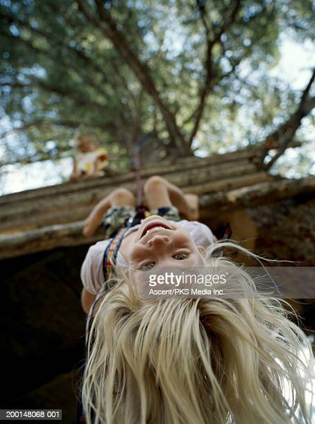 Girl (6-8) hanging upside down from tree fort, low angle view