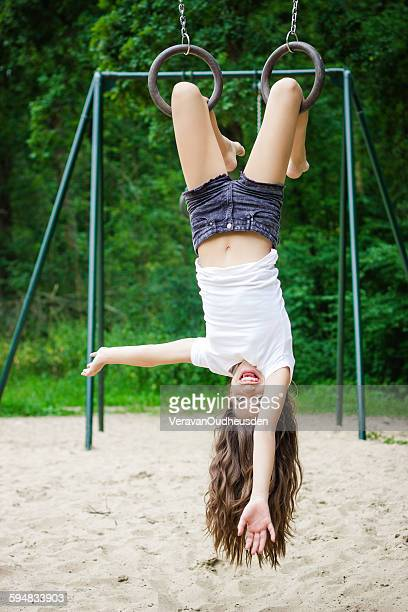 Girl hanging upside down in a playground