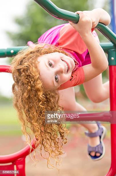 Girl Hanging Upside Down on Jungle Gym at Playground