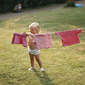 Girl (3-5) hanging washing on clothes line