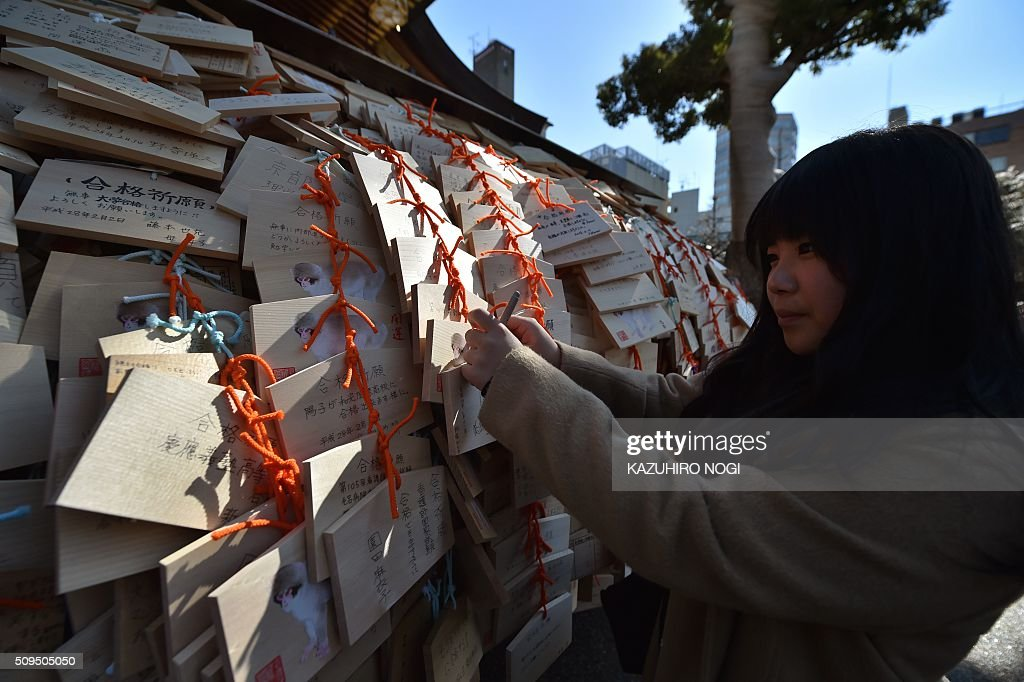 A girl hangs a small wooden votive tablet after writing her wishes on it, at Yushima Tenjin shrine in Tokyo on February 11, 2016. Every year many students and their parents come to the shrine to pray for success at exam time as the annual school entrance examination season started. AFP PHOTO / KAZUHIRO NOGI / AFP / KAZUHIRO NOGI