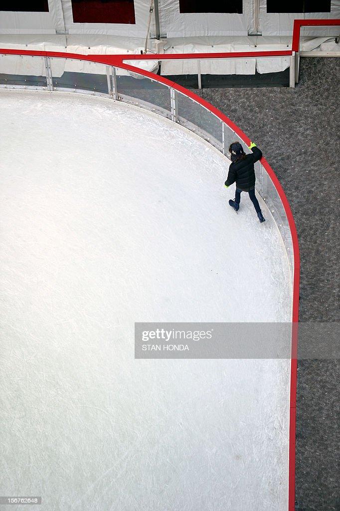 A girl hangs onto a railing as she ice skates at the Rockefeller Center ice rink November 20, 2012 in New York. AFP PHOTO/Stan HONDA