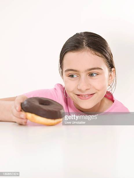 Girl happily holding a chocolate donut in her hand