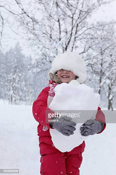 Girl happily holding giant snow ball.