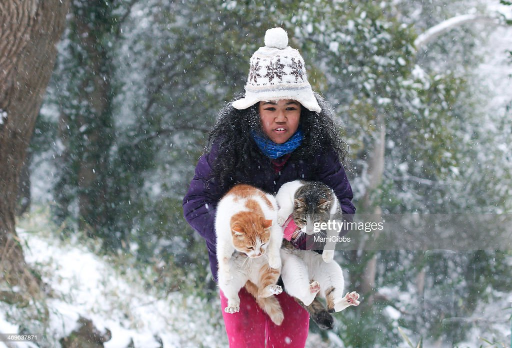 Girl has helped the cat out of the snow : Stock Photo