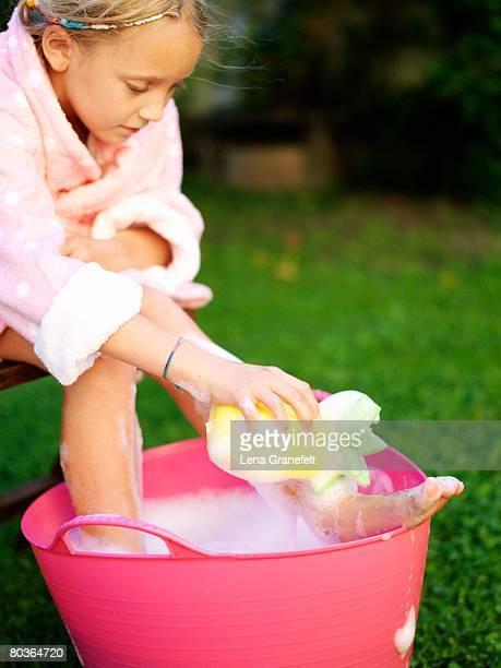 A girl having a footbath in the garden Sweden.