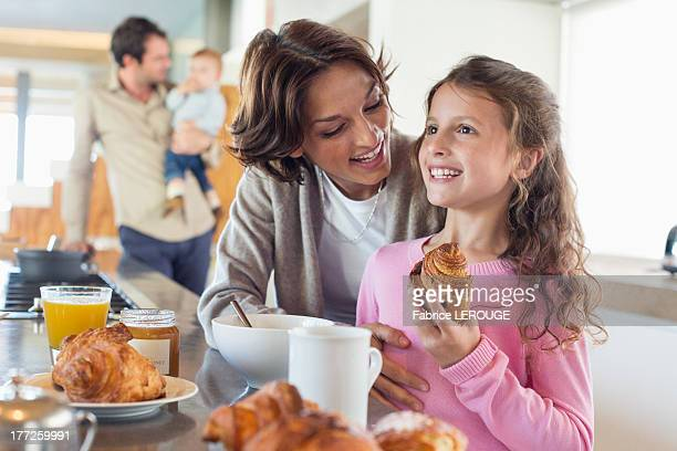 Girl having breakfast beside her mother at a kitchen counter