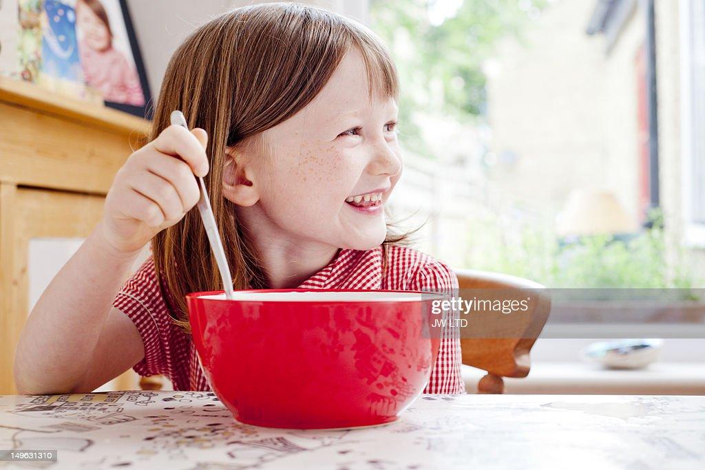 Girl (6-7) having cereals for breakfast : Stock Photo