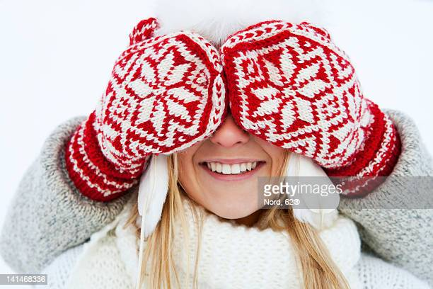 Girl having eyes covered by person wearing gloves