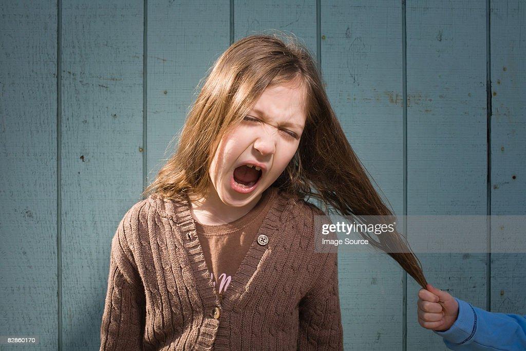 Girl having hair pulled
