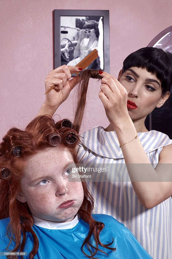 Girl (10-12) having hair styled in beauty parlor : Stock Photo