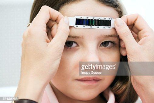 Girl having her temperature taken