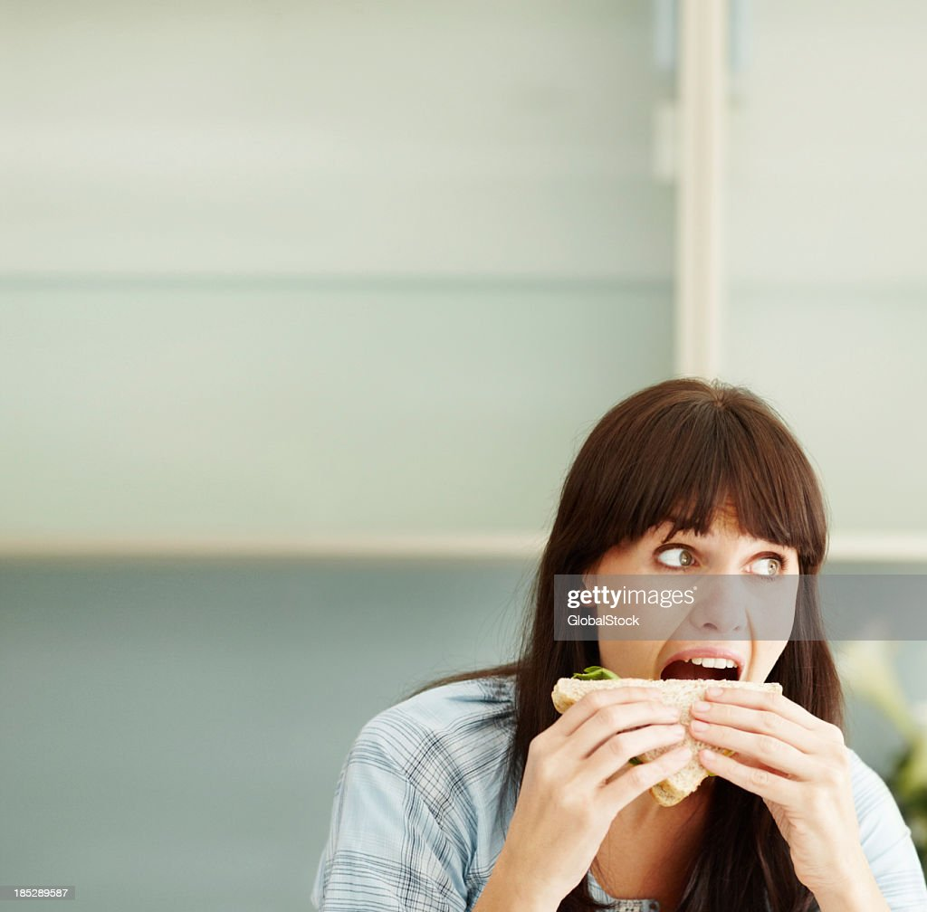 Girl having mouth open wide and munching a sandwich