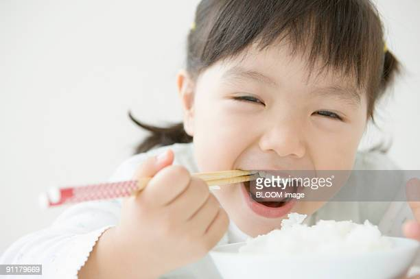 Girl having rice with chopsticks