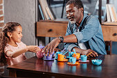African american girl having tea party with father at home